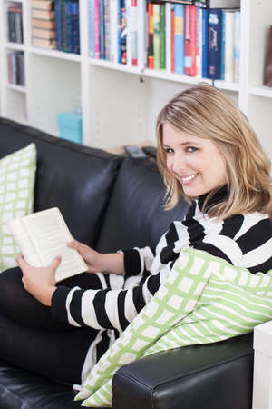 Young, beautiful woman sits on the couch and reads a book at home  A bookshelf is at the background  photo