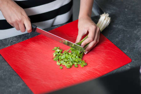 kitchen bench: Woman cuts leek on a kitchen bench in the kitchen Stock Photo