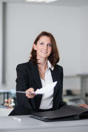 Young businesswoman hands over contract in office Stock Photo - 15599651