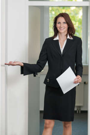 blazer: Businesswoman asks to come in into the office Stock Photo