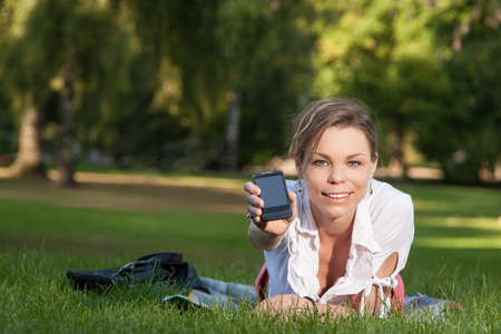 Young, attractive woman lies on a meadow in the park and shows her smartphone photo