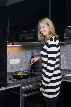fair haired: Pretty young woman is cooking in the kitchen  Stock Photo