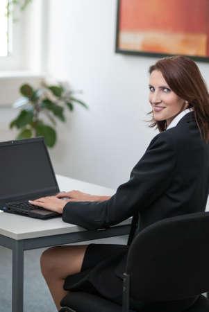 edv: Giovane imprenditrice attractice si trova in ufficio a un tavolo di fronte a lei taccuino e sorride all'osservatore