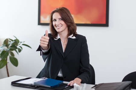 Young businesswoman sits in the office at the table and shows thumb up photo
