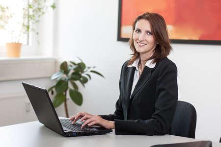 edv: Giovane imprenditrice attractice si trova in ufficio a un tavolo e usa il suo computer portatile