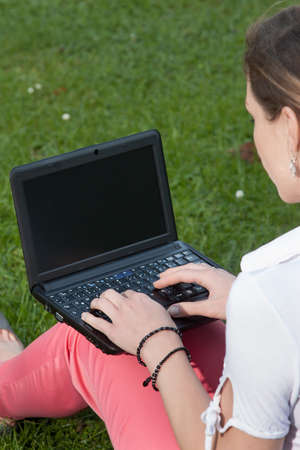 Woman sits on a meadow together with a netbook on her lap Stock Photo - 15687224