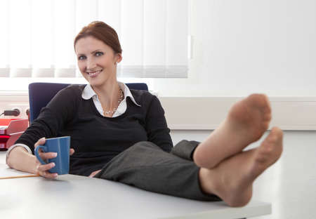desk clerk: Young woman makes a coffee break in the office while putting her legs up on the desk Stock Photo
