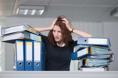 despaired: Businesswoman tears her hair due to many files she has to process Stock Photo