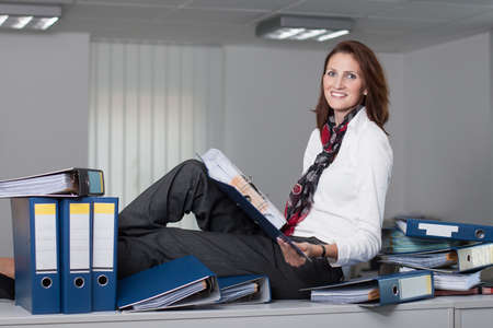 woman handle success: Attractive businesswoman sits on a desk surrounded by stacks of files