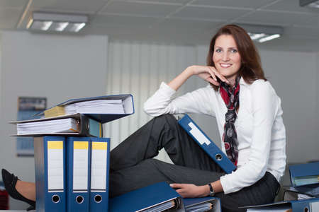 woman handle success: Businesswoman sits on the table surrounded by many files