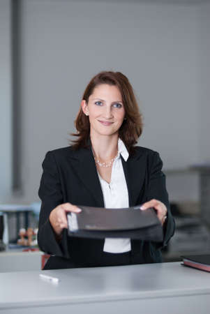 woman handle success: Young attractive businesswoman in an office presents documents Stock Photo