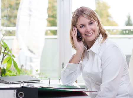 fair haired: Young fair-haired woman sits at the desk with files and phones with her smart phone