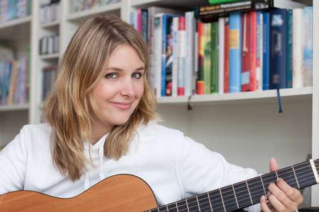 fair haired: Fair-haired woman plays guitar at home Stock Photo