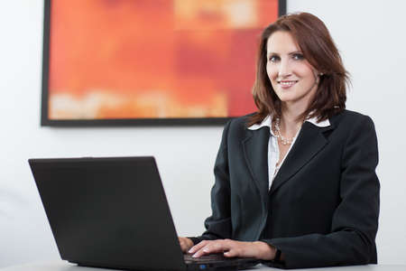 woman handle success: Young businesswoman sits in front of a notebook