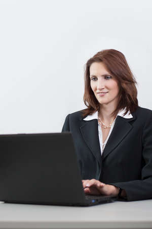 woman handle success: Young attractive businesswoman writes on a laptop Stock Photo