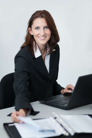 woman handle success: Young businesswoman at work with documents and notebook in the office