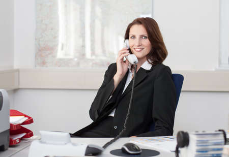 Young attractive businesswoman phones in her office Stock Photo - 16054817