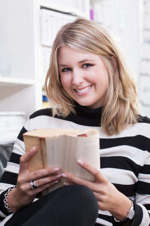fair haired: Young pretty woman reads a book Stock Photo