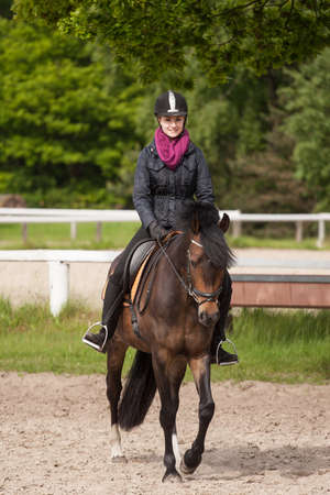 fair haired: Girl rides her brown horse  Stock Photo