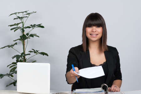 Woman sits at the desk and hands over a sheet of paper photo
