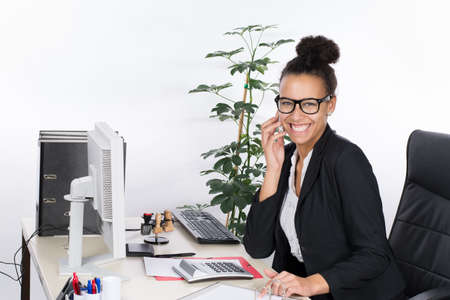 brazilian woman: Young, beautiful office worker sits at the desk in the office and phones with a smart phone