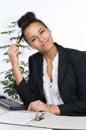 sympathetic: Young, beautiful office worker sits smiling at the desk in the office Stock Photo