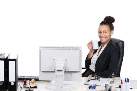 sympathetic: Young, beautiful office worker sits at the desk in the office and drinks a cup of coffee Stock Photo