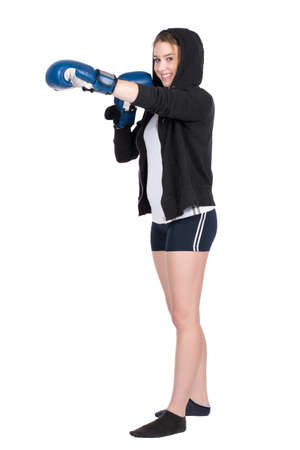 hoody: Cut out image of a young smiling woman wearing a hoody and blue boxing gloves who is boxing