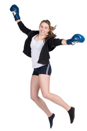 likeable: Cut out image of a young smiling female boxer wearing a hoody and blue boxing gloves, who is jumping