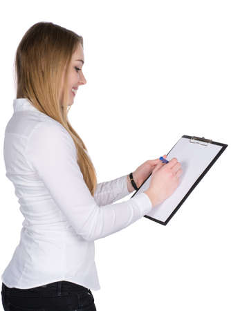 Cut out image of a young smiling woman who is writing at a clipboard while looking to the clipboard.