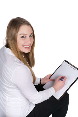 likeable: Cut out image of a young smiling woman who is writing at a clipboard while looking to the camera.