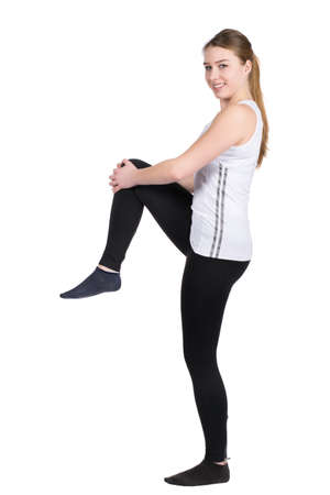 fair haired: Cut out image of a young woman who is stretching her leg musculature Stock Photo