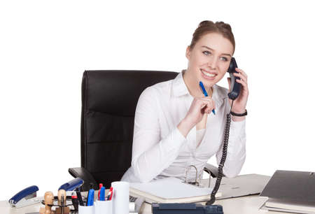 fair haired: Cut out image of a young smiling woman who is phoning at the desk in front of her documents. Woman looks right. Stock Photo
