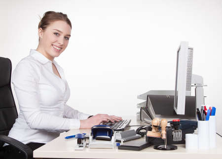 fair haired: Young smiling woman is typing at the keyboard while sitting at the desk. Woman looks to the camera.