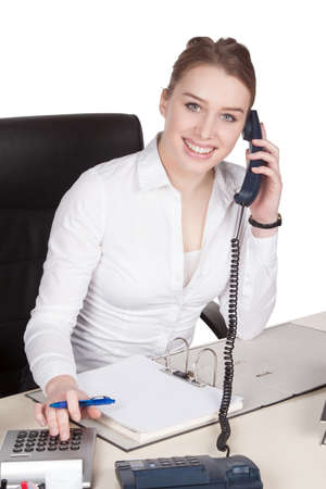 fair haired: Cut out image of a young smiling woman who is phoning at the desk in front of her documents while using the desk calculator