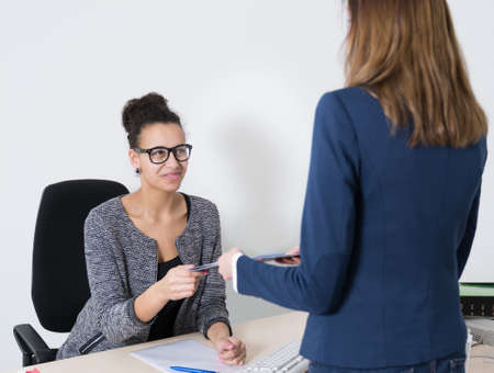 likable: One office clerk is handing over a document to another woman who is sitting at the desk in the office.