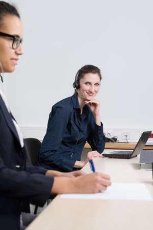 A young business woman with headset is sitting in front of a notebook. Another woman is sitting in the foreground (blurred) and is writing to a document. photo