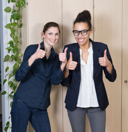 likeable: Two businesswomen are standing side by side and are holding her thumbs up. Stock Photo