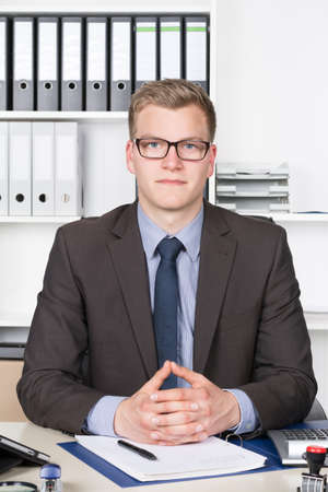 Young businessman is sitting with folded hands at the desk in the office  photo