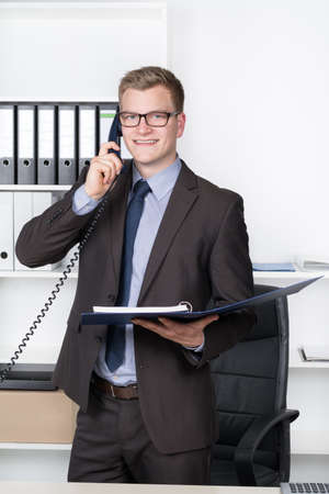 Young smiling businessman with glasses is phoning while standing at the desk in the office photo