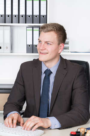fair haired: Young smiling businessman is typing at the computer keyboard while sitting at the desk in the office. Stock Photo