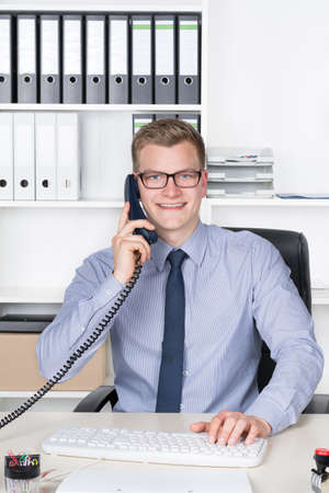 Young smiling businessman with glasses is phoning and typing at the computer keyboard while sitting at the desk in the office. A shelf is in the background. The man is looking to the camera. Stock Photo
