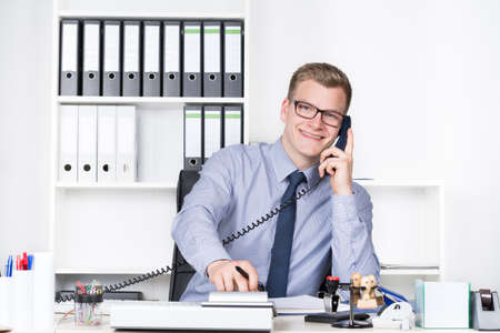 Young smiling businessman with glasses is phoning and typing at a desk calculator while sitting at the desk in the office. A shelf is in the background. The man is looking to the camera. photo