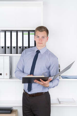 fair haired: Young businessman is holding an opened file while standing in front of a shelf in the office. The man is looking to the camera.