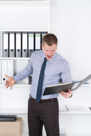Young furious businessman is looking into an opened file while standing in front of a shelf in the office. photo