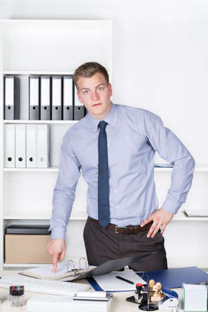 fair haired: Young businessman is pointing into an opened file with his finger while standing in front of a shelf in the office. The man is looking to the camera.
