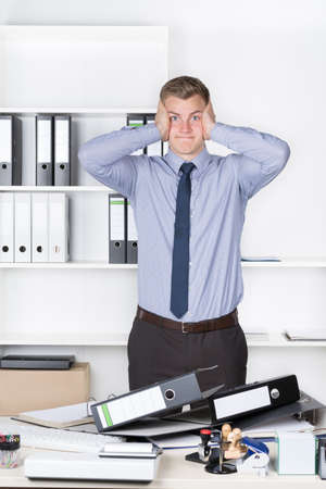 despaired: Young despaired businessman is standing in front of many files on his desk in the office. A shelf is in the background. The man is looking to the camera.