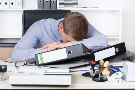 front desk: Young exhausted businessman is lying on his desk in the office in front of many files.