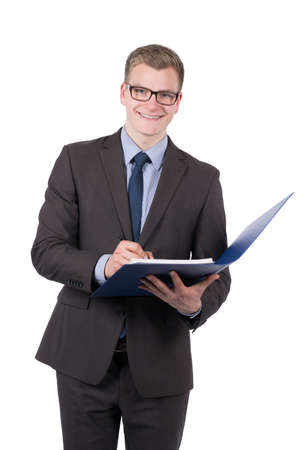 a young smiling businessman who is writing into a blue opened file photo