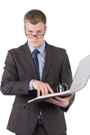 sceptical: Cut out image of a young sceptical businessman who is looking over his glasses while holding an opened file
